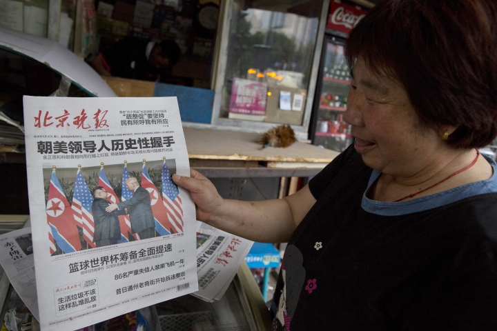 """FILE - In this June 12, 2018, file photo, a newspaper vendor holds up a front page photo of the meeting in Singapore between U.S. President Donald Trump and North Korean leader Kim Jong Un at a newsstand in Beijing, China. As soon as Kim steps off the airplane China provided him for the Singapore trip, Beijing will be mindful of maintaining its influence over a Pyongyang that may feel less isolated after Trump showered Kim with praises, called him a """"very talented man,"""" and made security concessions in return for very little. (AP Photo/Ng Han Guan, File)"""