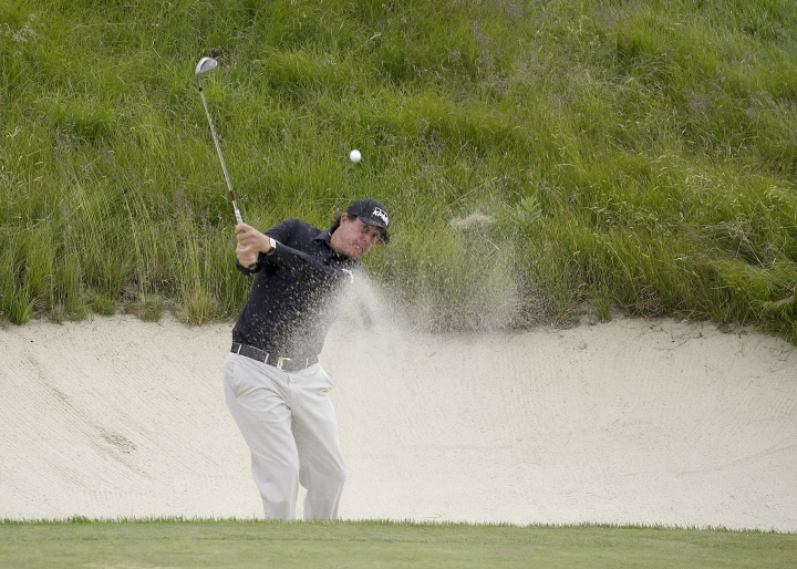 Phil Mickelson hits out of a bunker during a practice round for the U.S. Open Golf Championship, Wednesday, June 13, 2018, in Southampton, N.Y. (AP Photo/Seth Wenig)
