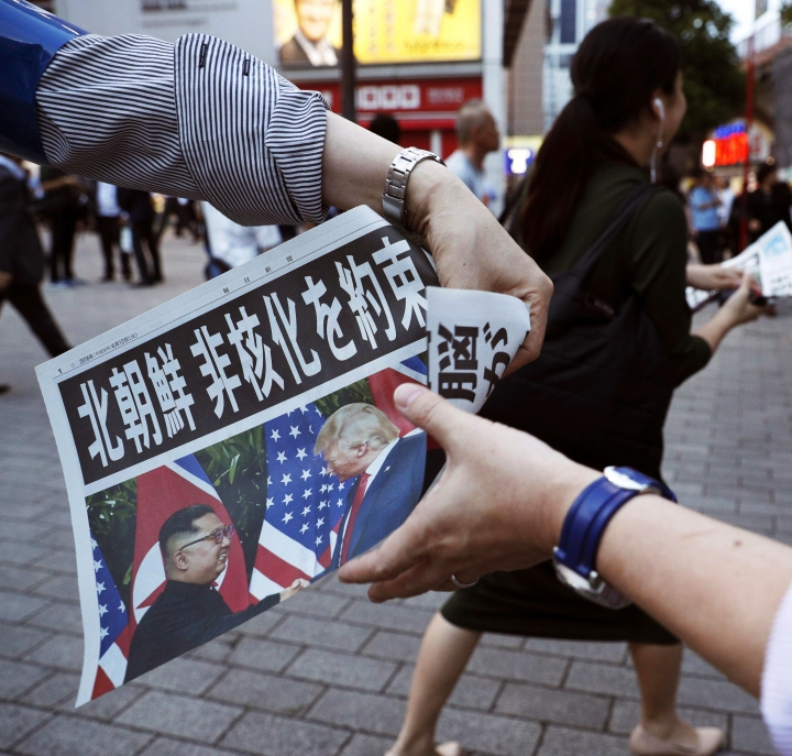 """A staff of Japanese newspaper Mainichi Shimbun distributes their extra edition which report the summit between U.S. President Donald Trump and North Korean leader Kim Jong Un in Singapore, near Shimbashi Station in Tokyo, Tuesday, June 12, 2018. The headline reads, """"North Korea promises to denuclearize"""". (Suo Takekuma/Kyodo News via AP)"""