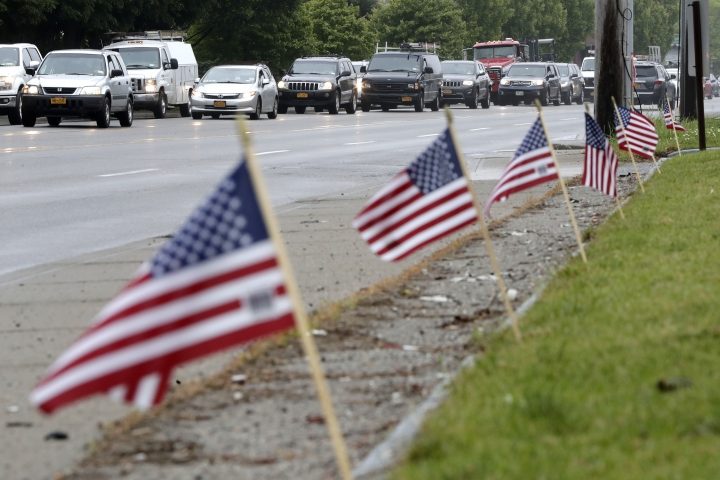 Flags adorning the front of a gas station wave as vehicles stand in traffic along County Road 39 near the site of the U.S. Open Golf Championship, Wednesday, June 13, 2018, in Southampton, N.Y. (AP Photo/Julio Cortez)