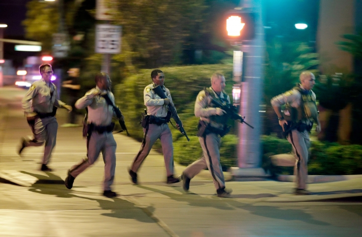 FILE - In this Oct. 1, 2017, file photo, police run toward the scene of a shooting near the Mandalay Bay resort and casino on the Las Vegas Strip in Las Vegas. Police planned to release body-worn camera video from officers who responded to the deadliest shooting in the nation's modern history last year on the Las Vegas Strip. The material released Wednesday, June 13, 2018, represents the sixth batch of Oct. 1 shooting material released since May 30 without comment by Clark County Sheriff Joe Lombardo or his department. Fifty-eight people died and hundreds were injured before authorities say the gunman, Stephen Paddock, killed himself before police reached him. (AP Photo/John Locher, File)