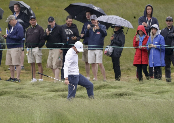 Rory McIlroy, of Northern Ireland, checks his lie in the fescue during a practice round for the U.S. Open Golf Championship, Wednesday, June 13, 2018, in Southampton, N.Y. (AP Photo/Frank Franklin II)