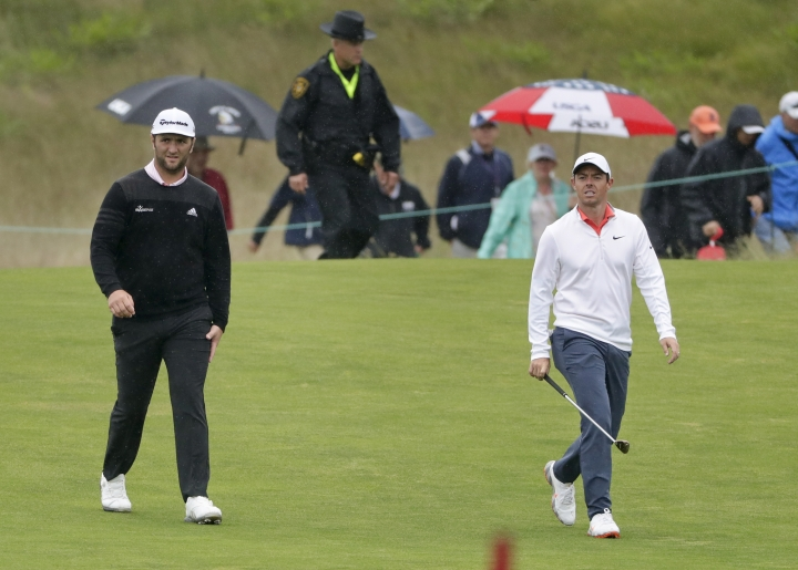 Jon Rahm, of Spain, left, walks with Rory McIlroy, of Northern Ireland, during a practice round for the U.S. Open Golf Championship, Wednesday, June 13, 2018, in Southampton, N.Y. (AP Photo/Frank Franklin II)