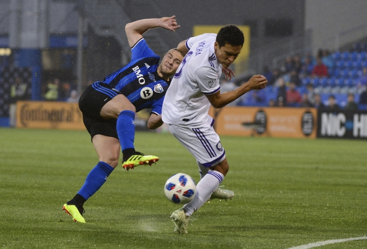 Orlando City midfielder Tony Rocha, right, edges the ball away from Montreal Impact midfielder Samuel Piette during the first half of an MLS soccer match Wednesday, June 13, 2018, in Montreal. (Paul Chiasson/The Canadian Press via AP)