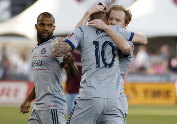 Chicago Fire forward Aleksandar Katai, center, is hugged by midfielder Dax McCarty, right, as defender Kevin Ellis looks over at them after Katai's goal against Colorado Rapids goalkeeper Tim Howard during the first half of an MLS soccer match Wednesday, June 13, 2018, in Commerce City, Colo. (AP Photo/David Zalubowski)
