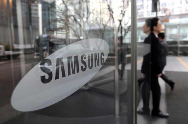 FILE - In this Jan. 31, 2018, file photo, an employee walks past a logo of the Samsung Electronics Co. at its office in Seoul, South Korea. Samsung Electronics, the world's biggest smartphone maker, pledged on Thursday, June 14, 2018, to convert its operations in the United States, Europe and China to using only solar and other renewable energy by 2020. (AP Photo/Ahn Young-joon, File)