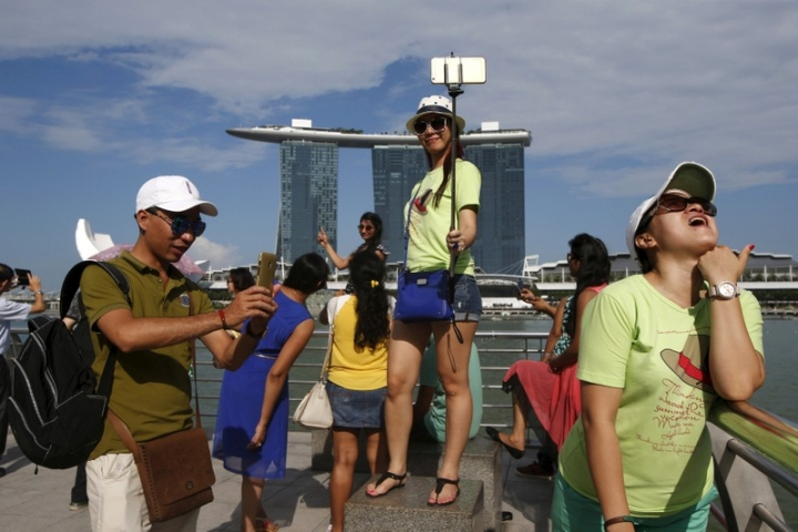 FILE PHOTO: Tourists pose for photos with the Marina Bay Sands and the Merlion statue (unseen) at a popular tourist spot along Marina Bay in Singapore July 24, 2015.  REUTERS/Edgar Su/File Photo