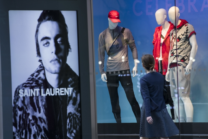 FILE- In this June 6, 2018, photo, an advertisement for Saint Laurent is seen on a bus stop display as a pedestrian walks past a window display at the Lord & Taylor flagship store on Fifth Avenue in New York. On Thursday, June 14, the Commerce Department releases U.S. retail sales data for May. (AP Photo/Mary Altaffer, File)