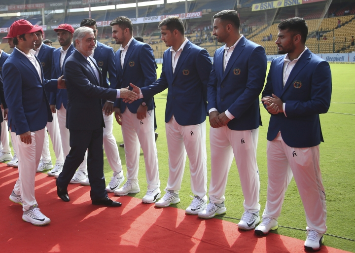 Afghanistan cricket team captain Asghar Stanikzai, left, introduces his team members to Afghanistan Chief Executive Abdullah Abdullah, second left, before the start of their one-off cricket test match against India in Bangalore, India, Thursday, June 14, 2018. (AP Photo/Aijaz Rahi)