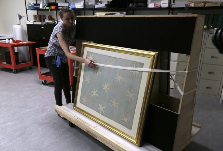 Collections manager Michelle Moskal secures the Commander-in-Chief's Standard, Wednesday, June 13, 2018, before moving it to an exhibition gallery at the Museum of the American Revolution in Philadelphia. The faded and fragile blue silk flag marked General George Washington's presence on the battlefield during the Revolutionary War. The museum is bringing the flag out of its archives for public viewing on Thursday, June 14, Flag Day, until Sunday. Its appearance at the museum is the flag's first public display in Philadelphia since the war. (AP Photo/Jacqueline Larma)