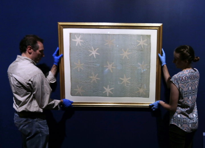 Collections manager Michelle Moskal, right, and curator Mark Turdo hang the Commander-in-Chief's Standard, Wednesday, June 13, 2018, at an exhibition gallery in the Museum of the American Revolution in Philadelphia. The faded and fragile blue silk flag marked General George Washington's presence on the battlefield during the Revolutionary War. The museum is bringing the flag out of its archives for public viewing on Thursday, June 14, Flag Day, until Sunday. Its appearance at the museum is the flag's first public display in Philadelphia since the war. (AP Photo/Jacqueline Larma)