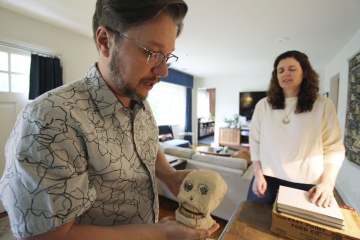 In this Tuesday, May 29, 2018 photo, Lance Ledbetter holds a piece of folk art in the shape of a skull as his wife, April, looks on at their home in Atlanta. The Ledbetters operate Dust-to-Digital, a record label that digitizes and re-releases old recordings. (AP Photo/Ron Harris)