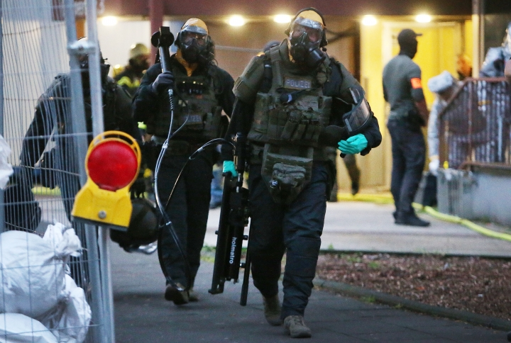 In this Tuesday June 12, 2018 photo, German police officers in protective gear leave an apartment building during an operation in Cologne, Germany. German police are searching the apartment of a 29-year-old Tunisian man who is accused of keeping toxic substances in his home. (David Young/dpa via AP)