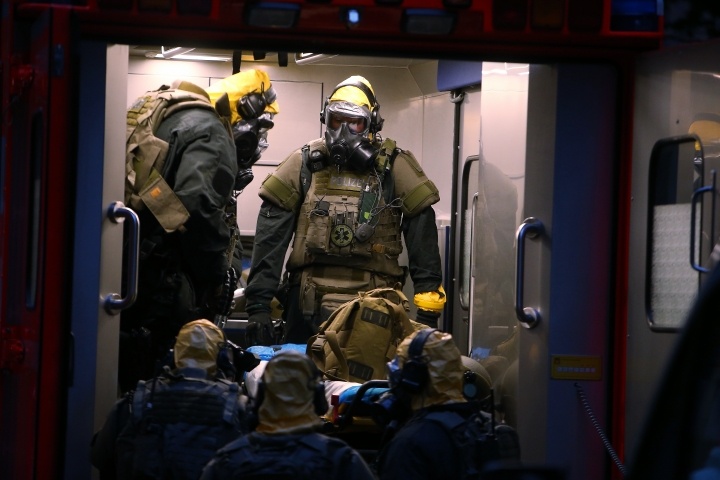 German police officers in protective gear enters a rescue car during an operation in Cologne, Germany, late Tuesday June 12, 2018. German police are searching the apartment of a 29-year-old Tunisian man who is accused of keeping toxic substances in his home. (David Young/dpa via AP)
