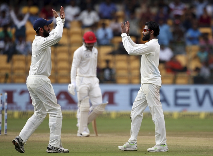 India's Ravindra Jadeja, right, celebrates with teammate Cheteshwar Pujara, left, the dismissal of Afghanistan's Rashid Khan, center, during the second day of one-off cricket test match in Bangalore, India, Friday, June 15, 2018. (AP Photo/Aijaz Rahi)