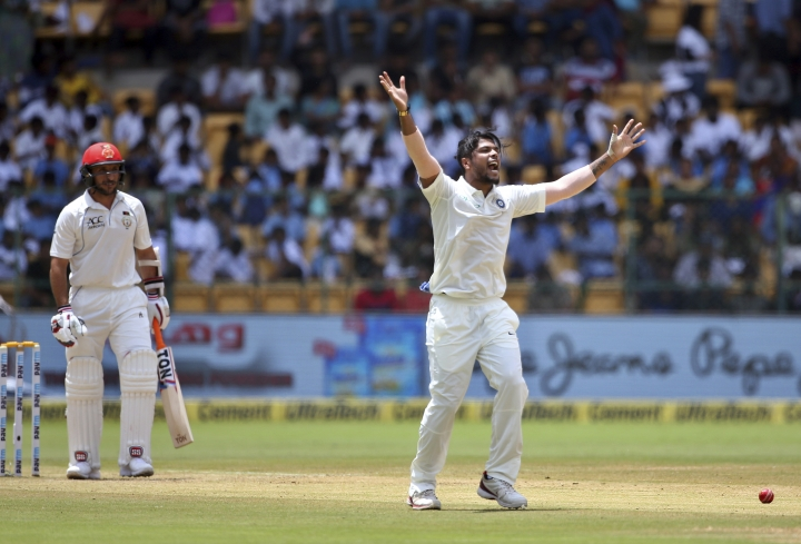 India's Umesh Yadav, right, appeals successfully for the wicket of Afghanistan's Rahmat Shah, left, during the second day of their one-off cricket test match in Bangalore, India, Friday, June 15, 2018. (AP Photo/Aijaz Rahi)