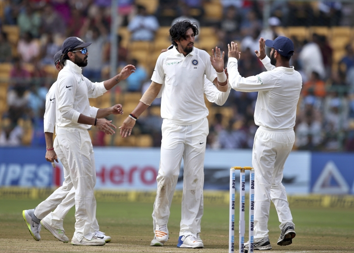 India's Ishant Sharma, center, celebrates with teammates the dismissal of Afghanistan's Rahmat Shah during the second day of their one-off cricket test match in Bangalore, India, Friday, June 15, 2018. (AP Photo/Aijaz Rahi)