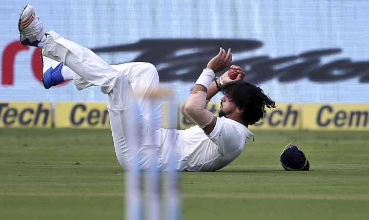 India's Ishant Sharma falls on the ground after taking the catch to dismiss Afghanistan's Mohammad Nabi during the second day of their one-off cricket test match in Bangalore, India, Friday, June 15, 2018. (AP Photo/Aijaz Rahi)