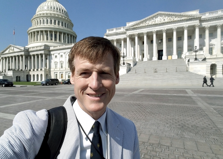 "In this Aug. 2, 2017 photo released by Jamie Dupree, Dupree, a Cox Media Group radio reporter, poses in front of the U.S. Capitol in Washington. Two years ago, Dupree encountered what others in his profession might see as an unsurmountable challenge: He lost his voice. Now he may have found a solution. A Scottish company that creates text-to-speech technology has crafted a new ""voice"" for Dupree: software turns his typed sentences into spoken words. (Jamie Dupree via AP)"