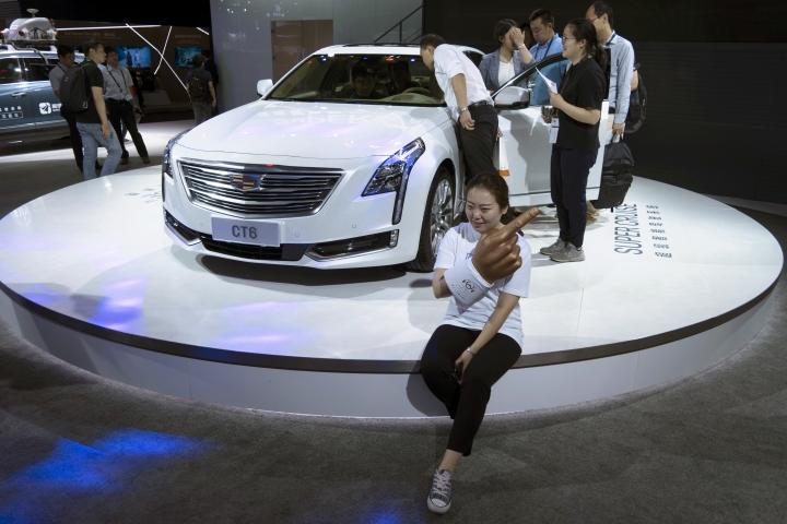 A woman poses for a photo in front of a CT6 Cadillac during the Consumer Electronics Show Asia 2018 in Shanghai, China on Friday, June 15, 2018. President Donald Trump is hiking the price of Chinese-made forklift trucks and X-ray machines for American buyers. They are part of a $50 billion list of Chinese exports targeted for a 25 percent tariff hike in response to complaints Beijing steals or pressures foreign companies to hand over technology. (AP Photo/Sam McNeil)