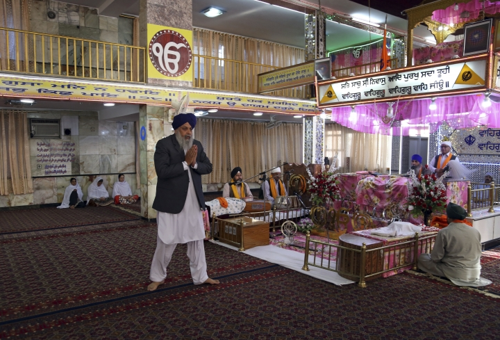 In this Thursday, June 7, 2018 photo, Avtar Singh Khalsa, a longtime leader of the Sikh community, who will represent Afghanistan's tiny Sikh and Hindu minority in the next parliament, prays, inside a colorfully decorated gurdwara, a place of worship for Sikhs, in Kabul, Afghanistan. Few Afghans are as invested in the government's quest for peace and stability as the dwindling Sikh and Hindu minorities, which have been decimated by decades of conflict. (AP Photo/Rahmat Gul)