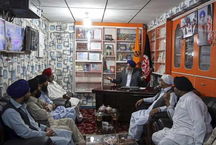 In this Thursday, June 7, 2018 photo, Avtar Singh Khalsa, a Sikh and longtime leader of the community, who will represent Afghanistan's tiny Sikh and Hindu minority in the next parliament, holds a meeting in his office, in Kabul, Afghanistan. Few Afghans are as invested in the government's quest for peace and stability as the dwindling Sikh and Hindu minorities, which have been decimated by decades of conflict. (AP Photo/Rahmat Gul)