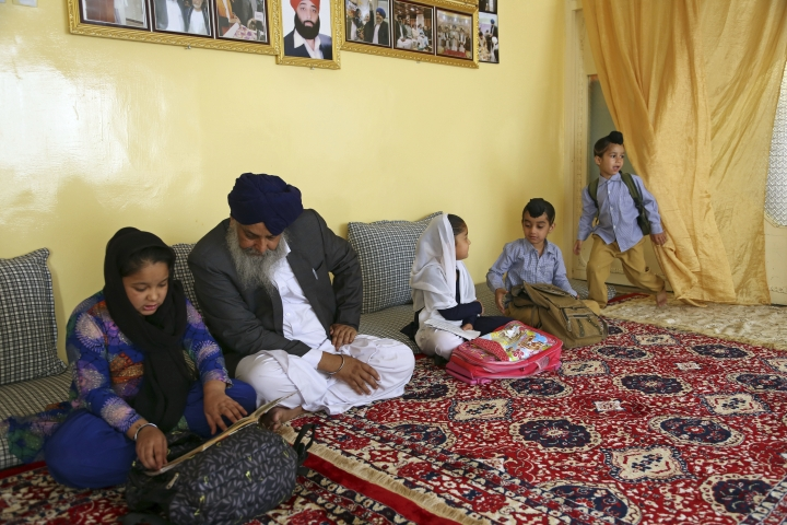 In this Thursday, June 7, 2018 photo, Avtar Singh Khalsa, a Sikh and longtime leader of the community, who will represent Afghanistan's tiny Sikh and Hindu minority in the next parliament, studies with his grandchildren at home, in Kabul, Afghanistan. Few Afghans are as invested in the government's quest for peace and stability as the dwindling Sikh and Hindu minorities, which have been decimated by decades of conflict. (AP Photo/Rahmat Gul)