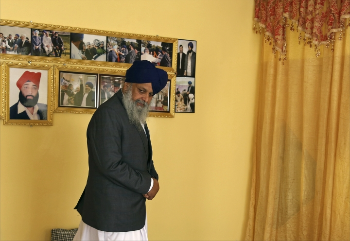 In this Thursday, June 7, 2018 photo, Avtar Singh Khalsa, a Sikh and longtime leader of the community, who will represent Afghanistan's tiny Sikh and Hindu minority in the next parliament, stands in front of a display of photographs at home, in Kabul, Afghanistan. Few Afghans are as invested in the government's quest for peace and stability as the dwindling Sikh and Hindu minorities, which have been decimated by decades of conflict. (AP Photo/Rahmat Gul)