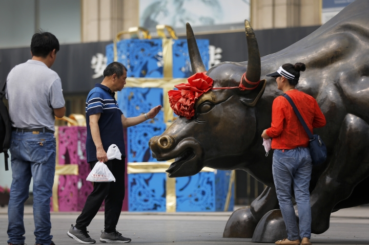 A man touches a bull statue as a couple preparing to take a picture outside a retail and wholesale clothing mall in Beijing, Monday, June 18, 2018. Asian shares were mostly lower Monday amid worries about trade tensions as the U.S. and China both started putting tariffs in motion. China and Hong Kong markets were closed for a national holiday. (AP Photo/Andy Wong)