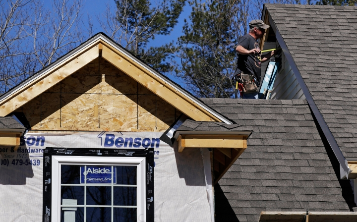 FILE- In this April 23, 2018, file photo, a worker installs vinyl siding on a new home in Auburn, N.H. On Monday, June 18, the National Association of Home Builders/Wells Fargo releases its June index of builder sentiment. (AP Photo/Charles Krupa, File)