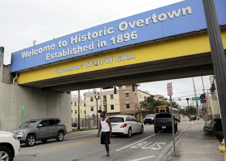 In this Monday, May 21, 2018 photo, a man crosses the street in the business district of the Overtown neighborhood of Miami. Celebrity chef Marcus Samuelsson has purchased a former pool hall in the neighborhood and plans to open a restaurant there. The redevelopment board is pouring tens of millions into restoring the historic neighborhood to its former glory. (AP Photo/Lynne Sladky)