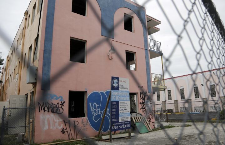 In this Monday, May 21, 2018 photo, a derelict apartment building, which is slated for rehabilitation, sits behind a chain link fence in the Overtown neighborhood of Miami. Celebrity chef Marcus Samuelsson has purchased a former pool hall in the neighborhood and plans to open a restaurant there. The redevelopment board is pouring tens of millions into restoring the historic neighborhood to its former glory. (AP Photo/Lynne Sladky)