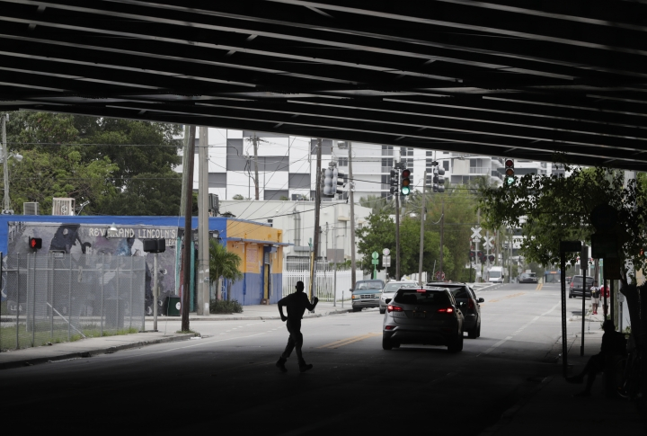 In this Monday, May 21, 2018 photo, a man crosses the street underneath the overpass of an expressway in the Overtown neighborhood of Miami. Celebrity chef Marcus Samuelsson has purchased a former pool hall in the neighborhood and plans to open a restaurant there. The redevelopment board is pouring tens of millions into restoring the historic neighborhood to its former glory. (AP Photo/Lynne Sladky)