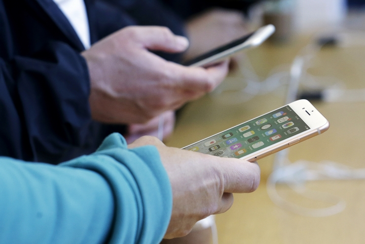 FILE - In this Sept. 22, 2017, file photo, customers look at iPhone 8 and iPhone 8 Plus phones at an Apple Store in San Francisco. Apple is trying to drag the U.S.'s antiquated system for handling 911 calls into the 21st century. (AP Photo/Jeff Chiu, File)