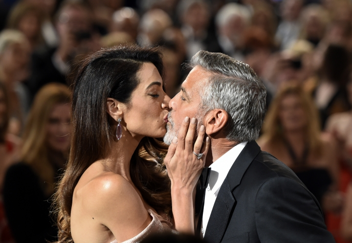 FILE - In this June 7, 2018 file photo, actor/director George Clooney gets a kiss from his wife Amal as he arrives for the 46th AFI Life Achievement Award in Los Angeles. The ceremony will air on Thursday, June 21. (Photo by Chris Pizzello/Invision/AP, FIle)
