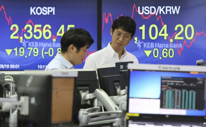 Currency traders work at the foreign exchange dealing room of the KEB Hana Bank headquarters in Seoul, South Korea, Tuesday, June 19, 2018. Asian stocks tumbled Tuesday after U.S. President Donald Trump escalated a dispute with Beijing over technology policy by threatening a tariff hike on additional Chinese goods. (AP Photo/Ahn Young-joon)