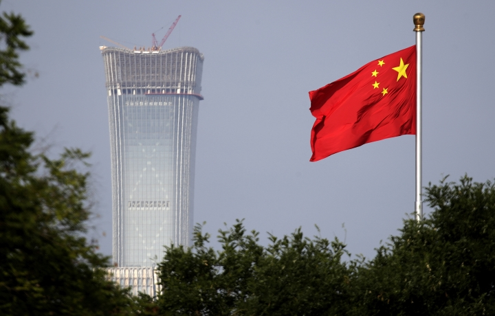 "FILE - In this Thursday, June 14, 2018, file photo, a Chinese national flag at Tiananmen Square flutters against the capital city tallest skyscraper China Zun Tower under construction at the Central Business District in Beijing. China has threatened ""comprehensive measures"" in response to U.S. President Donald Trump's new tariff hike, raising the possibility Beijing might target operations of American companies. (AP Photo/Andy Wong, File)"