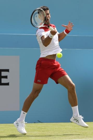 Novak Djokovic of Serbia plays a return to John Millman of Australia during their singles tennis match at the Queen's Club tennis tournament in London, Tuesday, June 19, 2018. (AP Photo/Kirsty Wigglesworth)