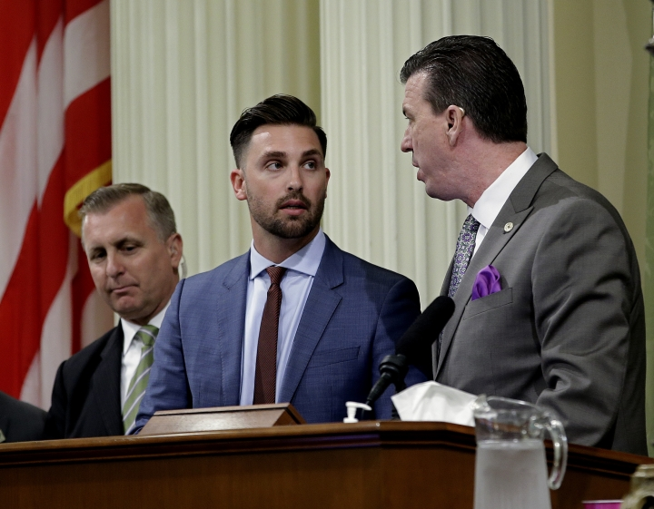 Assemblyman Ian Calderon, D-Whittier, center, talks with Assemblyman Kevin Mullen, D-South San Francisco, right, at the Capitol, Monday, June 18, 2018, in Sacramento, Calif. The Legislature approved a bill Calderon helped craft that aims to encourage better sexual harassment reporting and diverse hiring in the movie industry through the state's film tax credit program. The bill now goes to governor. (AP Photo/Rich Pedroncelli)