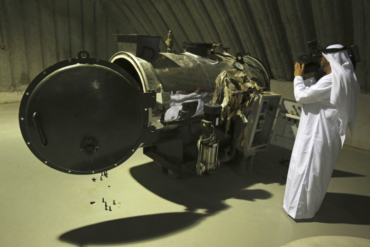 An Emirati journalist films what officials described as a heat exchanger used in the production of rocket fuel that they captured in Marib, Yemen, on display at a military installation in the United Arab Emirates, Tuesday, June 19, 2018. Officials involved in the Saudi-led campaign against Shiite rebels in Yemen known as Houthis showed journalists on Tuesday materiel captured on the battlefield that they alleged show Iran's hand in arming the rebels. Iran long has denied arming the Houthis, despite reports by the United Nations, Western countries and outside groups linking them to the rebels' arsenal. (AP Photo/Jon Gambrell)