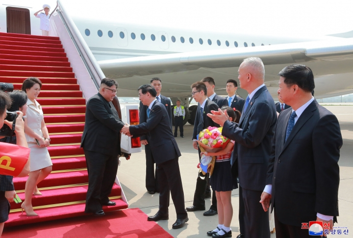 "In this June 19, 2018, photo provided on June 20, 2018, by the North Korean government, North Korean leader Kim Jong Un, second from left, and his wife Ri Sol Ju, left, are greeted by Wang Huning, member of the Politburo Standing Committee, on their arrival at Beijing Capital International Airport in Beijing, China. Korean language watermark on image as provided by source reads: ""KCNA"" which is the abbreviation for Korean Central News Agency. (Korean Central News Agency/Korea News Service via AP)"