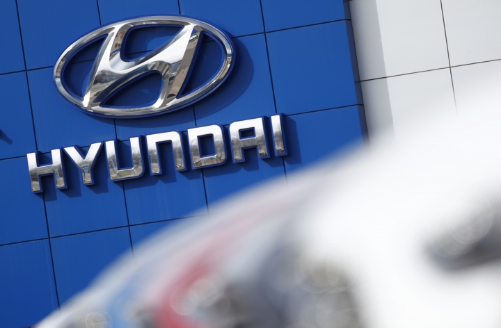 FILE- In this April 15, 2018, file photo the company logo hangs on the side of a showroom as a long row of unsold 2018 Sonatas sits on a Hyundai dealer's lot in the south Denver suburb of Littleton, Colo. The annual survey by J.D. Power finds that buyers reported a record-low 93 problems per 100 vehicles during the first three months of ownership, four problems fewer than last year. The survey also found that Korean brands Genesis, Kia and Hyundai claimed the top three spots for the first time in new vehicle quality. (AP Photo/David Zalubowski, File)