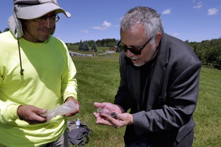 """In this June 14, 2018 photo, Wade Lawrence, right, museum director and senior curator at The Museum at Bethel Woods, looks at artifacts recovered from a dig at the site of the original Woodstock Music and Art Fair, in Bethel, N.Y. Edgar Alarcon of the Public Archaeology Facility at Binghamton University looks on at left. """"This is a significant historic site in American culture, one of the few peaceful events that gets commemorated from the 1960s,"""" said Lawrence. (AP Photo/Richard Drew)"""