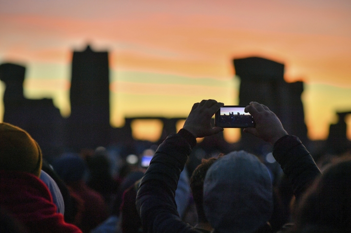 People take photos as the sun rises and shines through the stones at Stonehenge as crowds of people gather to celebrate the dawn of the longest day in the UK, in Wiltshire, England, Thursday June 21, 2018. The neolithic Wiltshire monument is built along the solstice alignment of the summer sunrise and the winter sunset. (Ben Birchall/PA via AP)