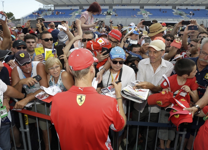 Ferrari driver Sebastian Vettel of Germany, back, signs autographs in the pit lane at the Paul Ricard racetrack, in Le Castellet, southern France, Thursday, June 21, 2018. The Formula one race will be held on Sunday. (AP Photo/Claude Paris)