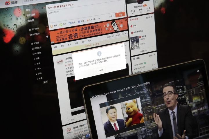 "A screen shows a failure message saying a post could not be sent because ""the content contains information that violates relevant laws and regulations"" on Sina Weibo next to a smaller computer screen showing a ""Last Week Tonight"" HBO show's host John Oliver with a photo of Chinese President Xi Jinping and Winnie the Pooh, in Beijing, Friday, June 22, 2018. The popular Chinese social media site is blocking users from posting about the show and its HBO host Oliver after the news satire program aired a segment this week making fun of Xi. (AP Photo/Andy Wong)"