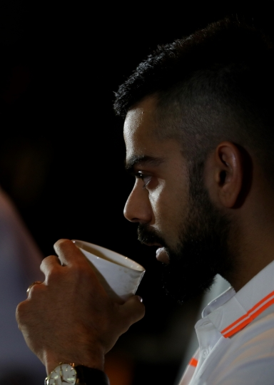 Indian cricket captain Virat Kohli, takes a sip as he addresses the media ahead of the team's travel to England and Ireland in New Delhi, India, Friday, June 22, 2018. (Manish Swarup)