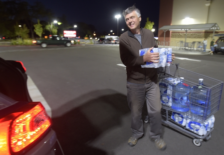 FILE - In this May 29, 2018 file photo, Floyd Oar of Salem loads his SUV with water purchased at WinCo in Albany, Ore. Oar purchased water for himself and his grown children's families who all reside in the Salem area. For several weeks the residents of Salem, Ore., were told the area's tap water was unsafe for the young, elderly or ill because of toxic algae blooms in the state capital's water source. (Mark Ylen/Albany Democrat-Herald via AP)