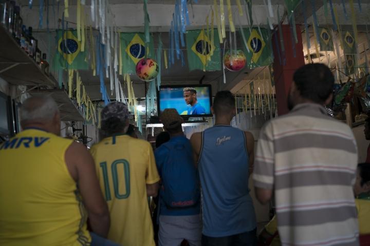 Brazilian soccer fans watch a live telecast of their team's World Cup match against Costa Rica, in a bar at the Alemao Complex slum in Rio de Janeiro, Brazil, Friday, June 22, 2018. Brazil won 2-0. (AP Photo/Leo Correa)
