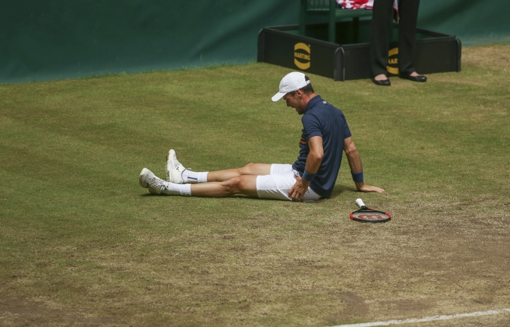 Roberto Bautista Agut lays injured on the court during the semi final match against Boran Coric at the Gerry Weber Open ATP tennis tournament in Halle, Germany, Saturday, June 23, 2018. (Friso Gentsch/dpa via AP)
